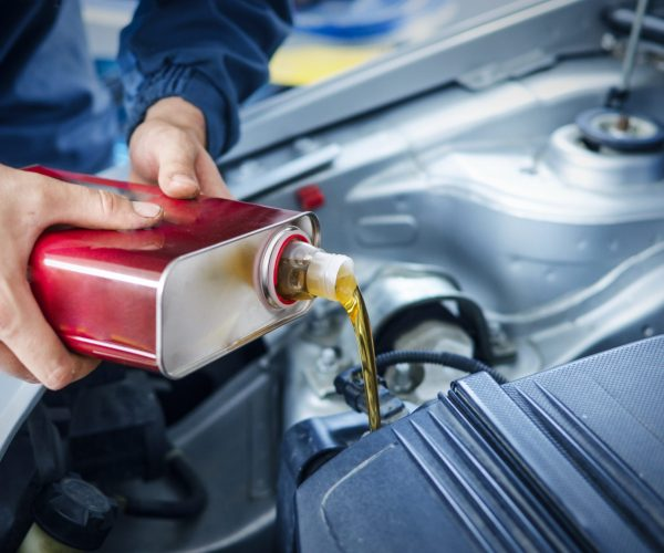 Mechanic changing engine oil on car vehicle.